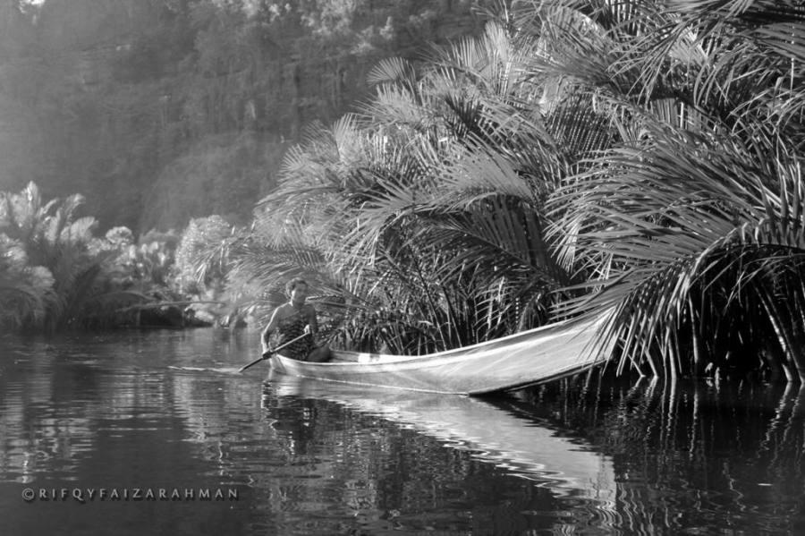 Seorang warga Dusun Berua mengayuh perahu menyusuri Sungai Pute