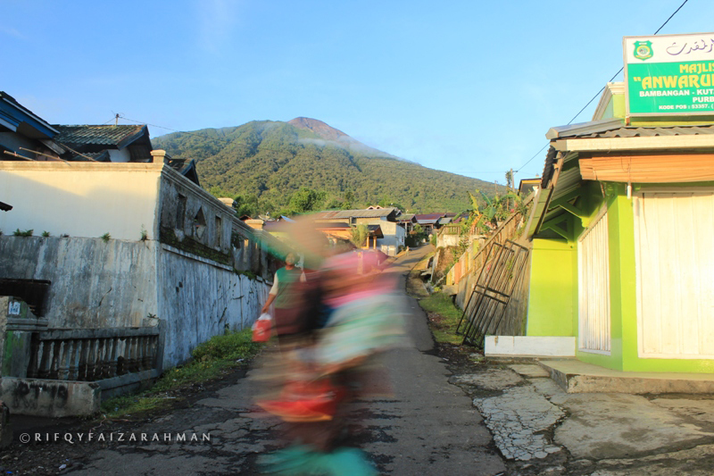 Warga dusun melintas di jalan kampung dengan latar belakang Gunung Slamet