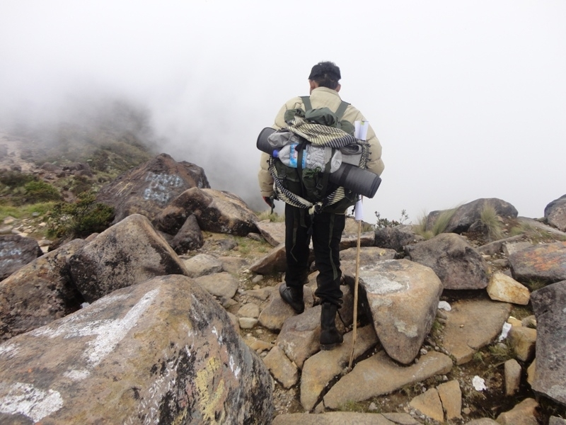 Dani berjalan di antara batu-batu besar yang tercoreng vandalisme di Puncak Ogal-Agil, Gunung Arjuno