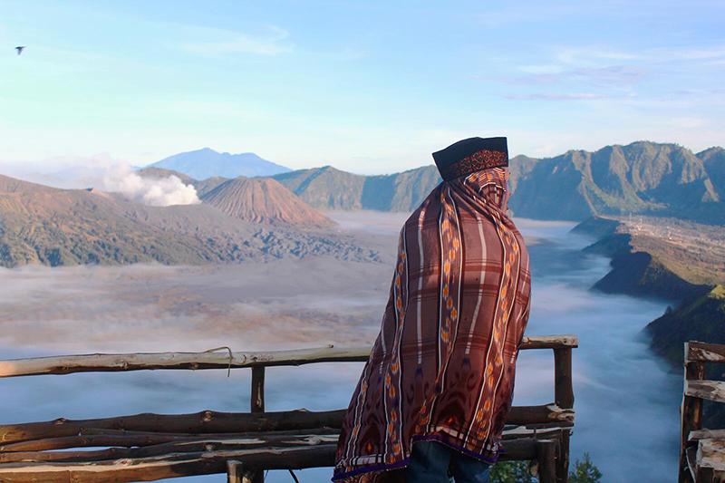 Seorang pria Tengger berbalut sarung dan mengenakan peci menikmati panorama Bromo