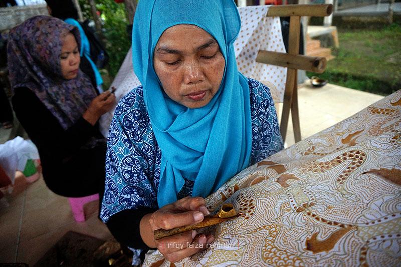 Nur Janah, seorang pengrajin, sedang mencanting di atas kain batik bermotif klasik