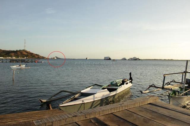 Tampak Pulau Kenawa (lingkaran merah) agak tertutup kapal feri yang berlabuh di Pelabuhan Poto Tano, Sumbawa Barat
