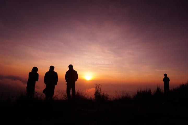 Siluet pendaki saat menyaksikan matahari terbit dari puncak Butak