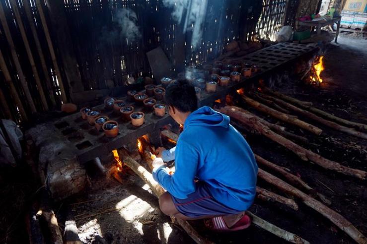 Syahrul mengecek kondisi api dan kayu bakar